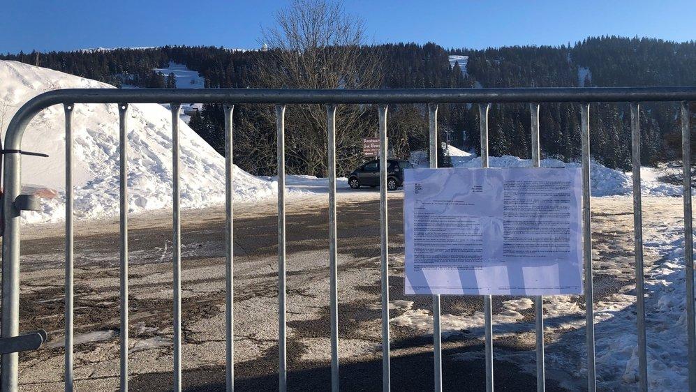 Des barrières vauban, sur lesquelles est affichée une copie du premier arrêté préfectoral du 29 décembre 2020, entravent l'accès au parking des Dappes, donc au domaine skiable suisse de la Dôle.