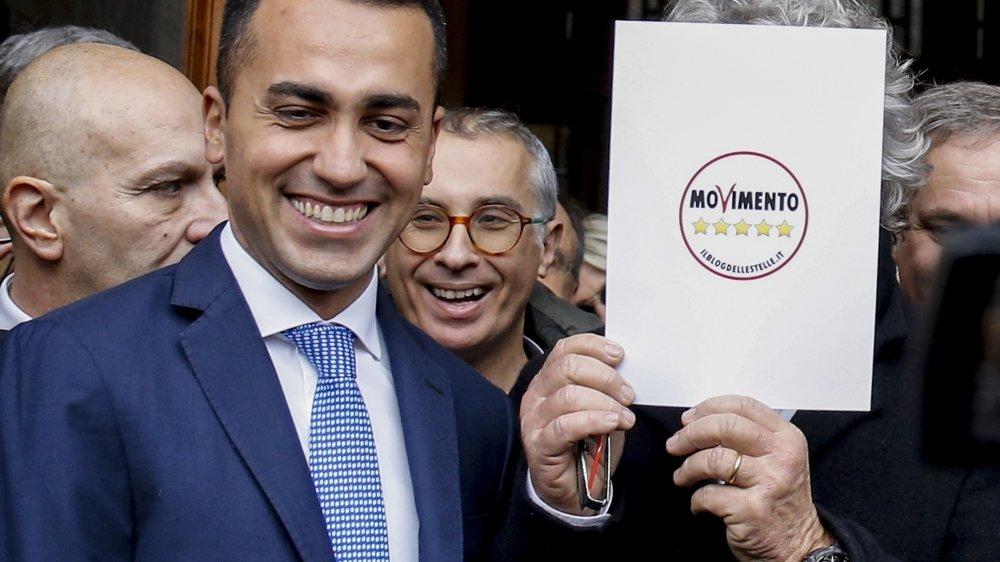 Le Mouvement fondé en 2009 par l'humoriste Beppe Grillo (derrière le carton, avec à g. leur député Luigi Di Maio) est au bord de la scission.
