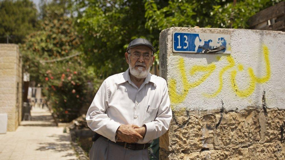 Un habitant du quartier de Cheikh Jarrah, à Jérusalem-Est, menacé d'expulsion forcée. Le graffiti en arabe  à côté de lui indique «nous ne partirons pas». La photo a été prise le 11 mai 2021.
