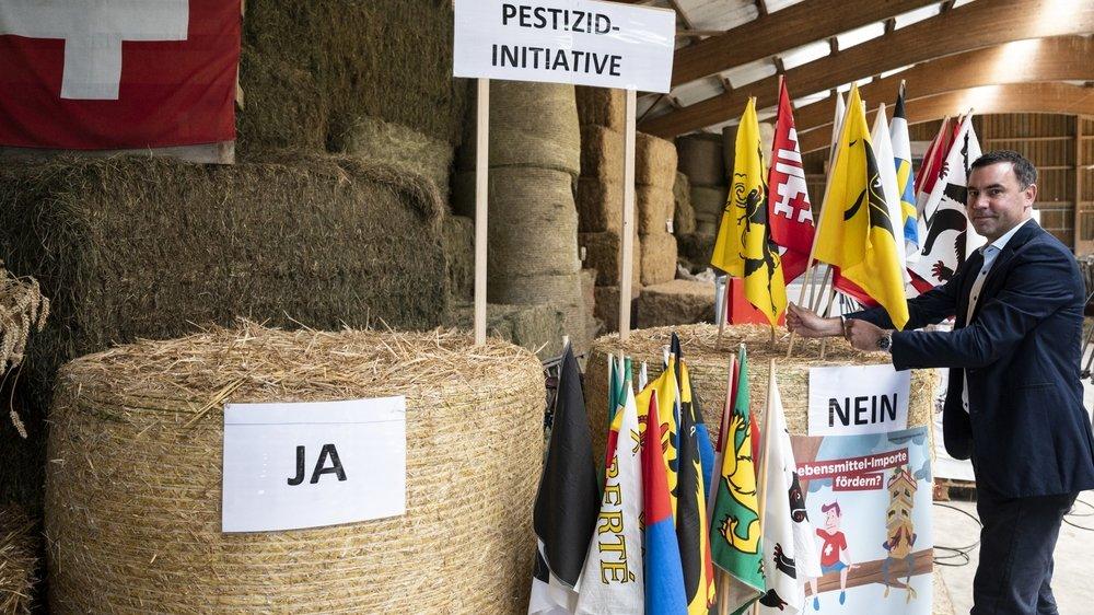 """Martin Rufer, directeur de l'Union suisse des paysans, place les drapeaux cantonaux correspondants dans la botte de foin du «Non"""" pour indiquer un résultat intermédiaire."""