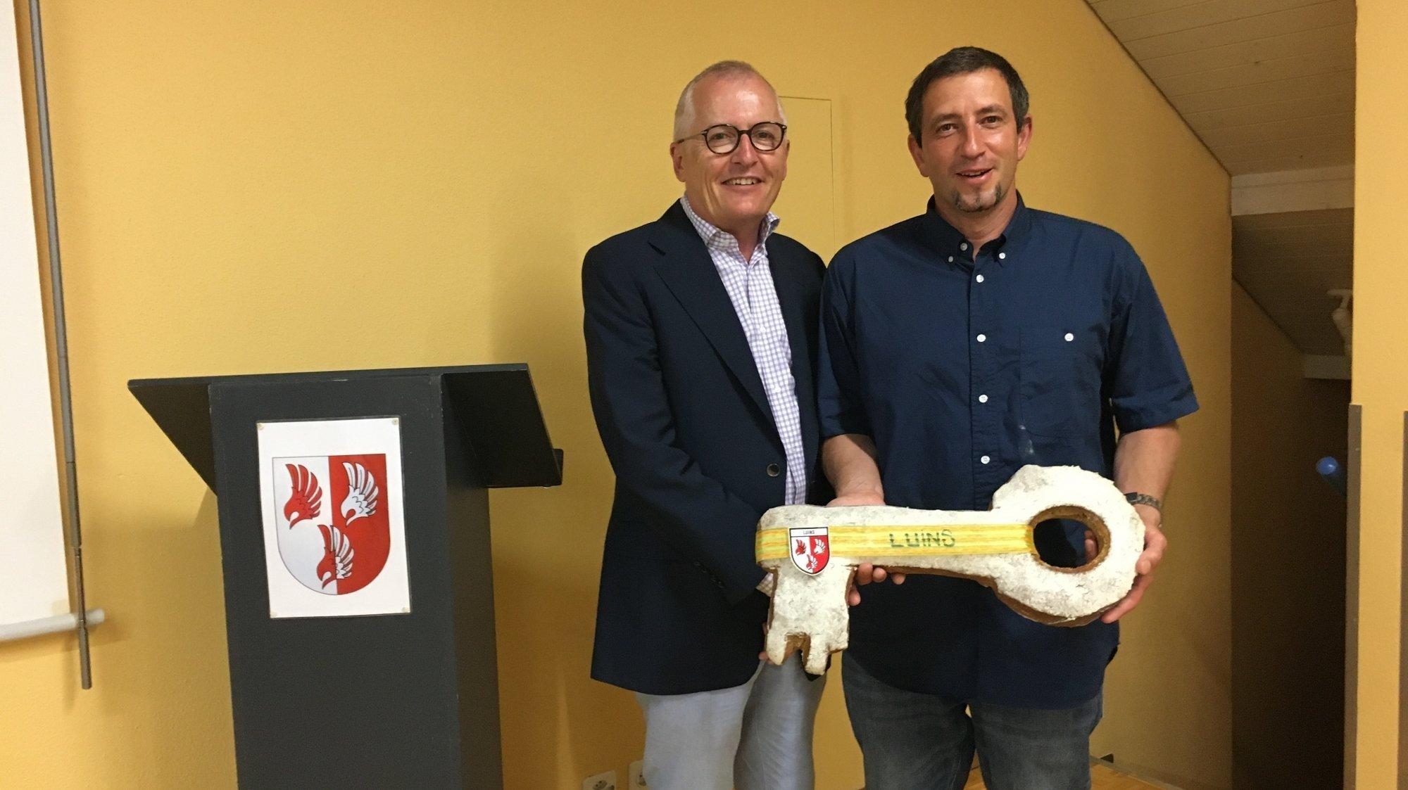 Claude Gaignard (à g.) a remis symboliquement les clés du village à son successeur Olivier Dutruy, un clin d'oeil goûteux fabriqué par le boulanger de Bursins.