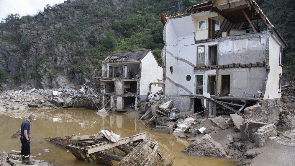 Un pompier se tient devant une maison complètement détruite dans le village de Mayschoss, en Allemagne, mardi 20 juillet 2021.