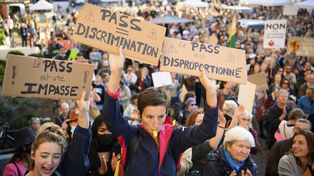 Des personnes brandissent des pancartes lors d'une manifestation contre l'obligation du certificat covid ce mardi 21 septembre 2021 a Lausanne. Environ 2000 personnes de plusieurs mouvements, dont des etudiants, ont manifestes dans les rue de Lausanne pour la liberte et contre le pass covid. (KEYSTONE/Laurent Gillieron)