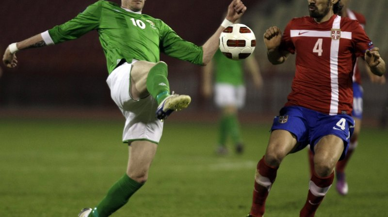 Kyle Lafferty of Northern Ireland, left, touches the ball ahead of Serbia's Milan Bisevac during their Euro 2012 Group C qualifying soccer match in Belgrade, Serbia, Friday, March 25, 2011. (AP Photo/ Marko Drobnjakovic)