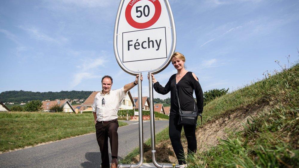 Les verres à pied représentent l'image vigneronne reflétée par le village de Féchy. Ici, les municipaux Marc Morandi et Francine Dupuis posent devant le panneau à l'entrée de la localité.