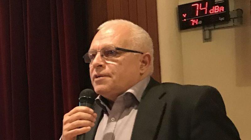 Claude Hilfiker, municipal à Mies, en plein discours, alors que le sonomètre affiche le volume sonore de la salle.