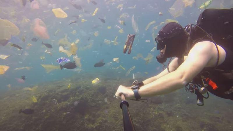 Il se filme en train de nager dans une mer de détritus