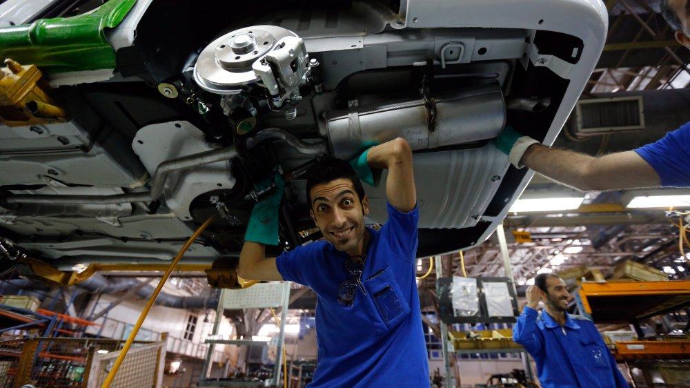 Des ouvriers du premier constructeur iranien, Iran Khodro, au travail. Cette entreprise, sise à Téhéran, assemble également des modèles  de la marque française Peugeot. Un partenariat qui pourrait être mis en danger avec le retour des sanctions américaines.