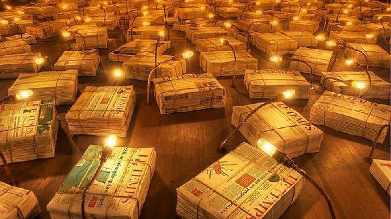 Des milliers d'exemplaires de journaux ficelés, éclairés par des lampes tamisées