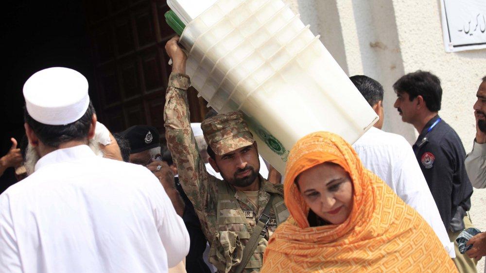 Selon les observateurs, l'armée du Pakistan joue un rôle important, ici un militaire installe des urnes.