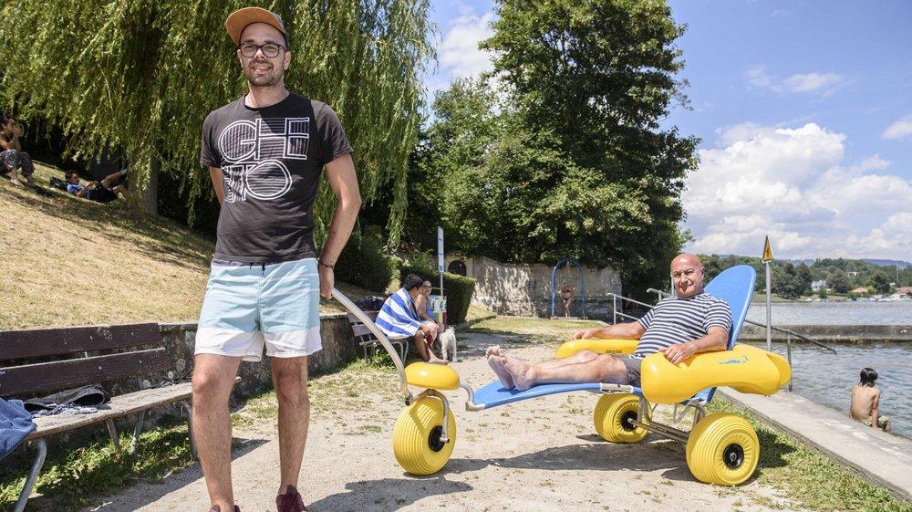 """A la plage de Gland, Rui Estima et Thierry Jacquet, qui prend la pose dans ce fauteuil """"tir à l'eau"""", aident les personnes en situation de handicap."""