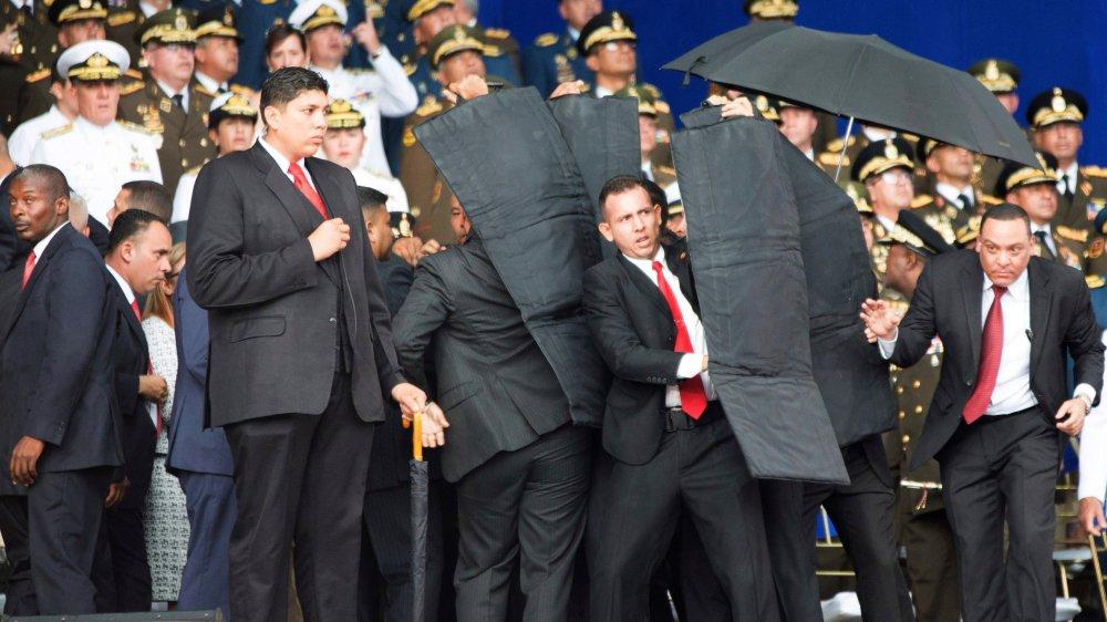 Nicolas Maduro (caché) a été protégé par tous les moyens, même un parapluie...