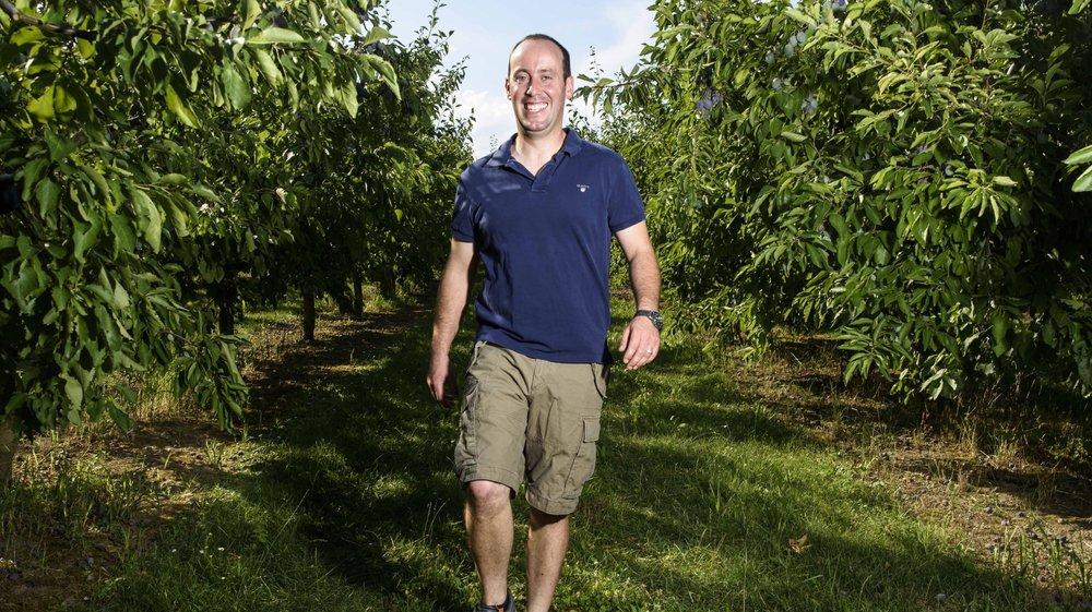 Lionel Cavin, producteur de pruneaux, parcourt le verger familial avec entrain.