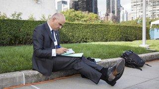 Ce cliché d'Alain Berset prenant des notes assis sur un trottoir fait le buzz sur la toile