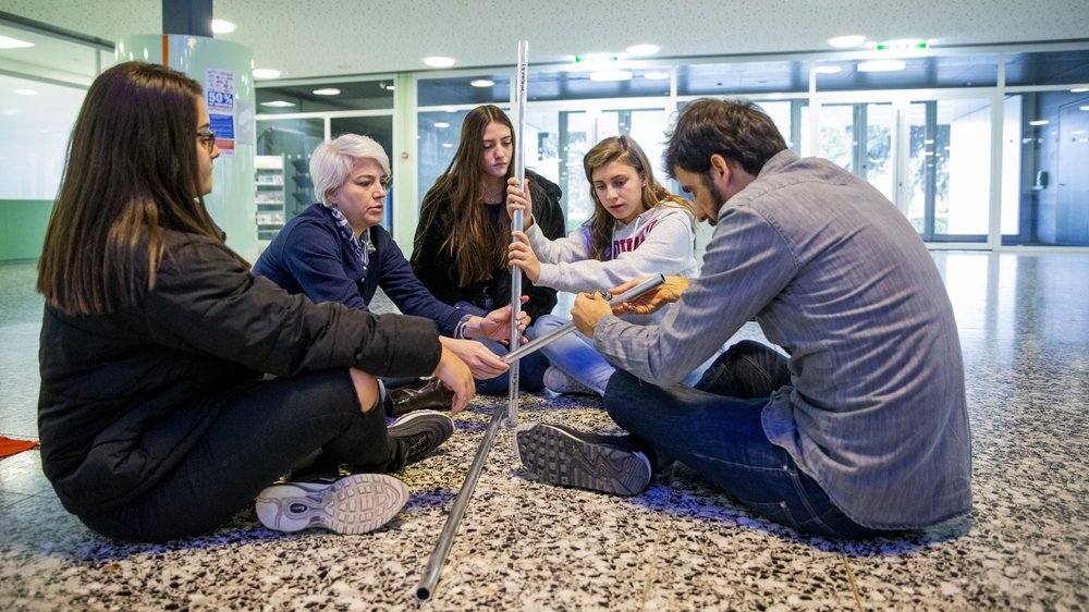 Les artistes brésiliens Carol Tonetti et Vitor Cesar aident les élèves à fixer leur création.