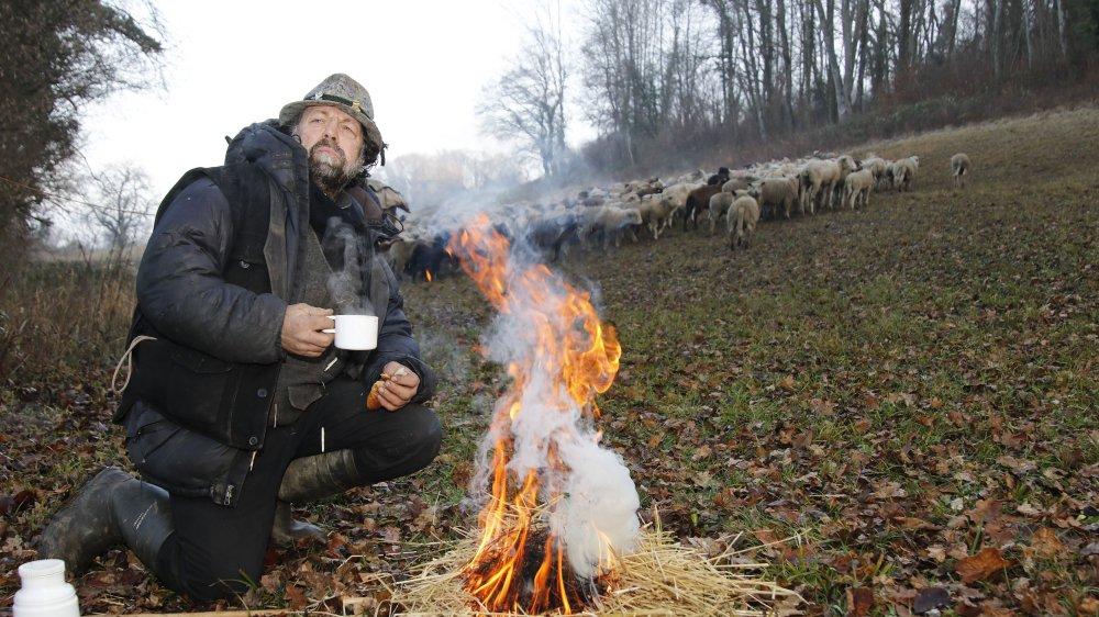 Avant d'entamer une longue marche avec ses bêtes, le berger Nicola Toscano profite d'une pause café à la chaleur d'un feu. Le Grison avait dormi dans sa fourgonnette à deux pas des moutons, à l'abri d'une clairière sous la commune de Bavois. Les agneaux et agnelles sont propriété des frères Benzoni à Aubonne.