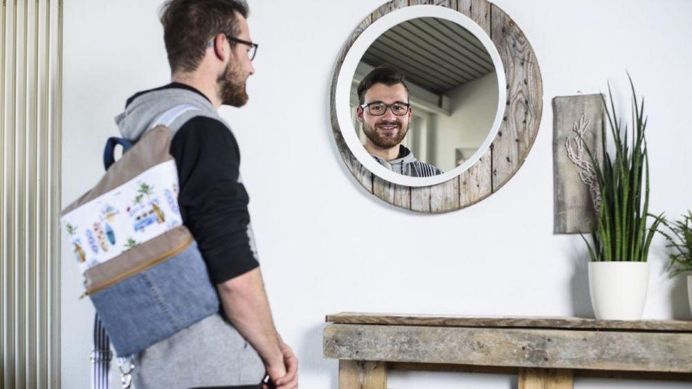 Samuel Monachon porte le sac qui lui a valu le prix de couture au milieu du hall du Centre d'enseignement des métiers de l'économie familiale qu'il a redécoré avec deux élèves et pour lequel il a aussi obtenu le prix de la décoration d'intérieur.