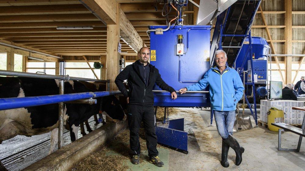 Thibault et Serge Melly devant le robot distribuant le fourage à leurs 60 vaches qui évoluent dans un univers automatisé sur fond de musique classique.