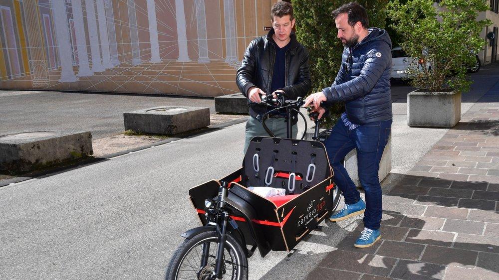 Jonas Schmid, de l'Académie de la mobilité du TCS, montre à Rémi Cabanes du café Milo, comment utiliser le vélo-cargo électrique.