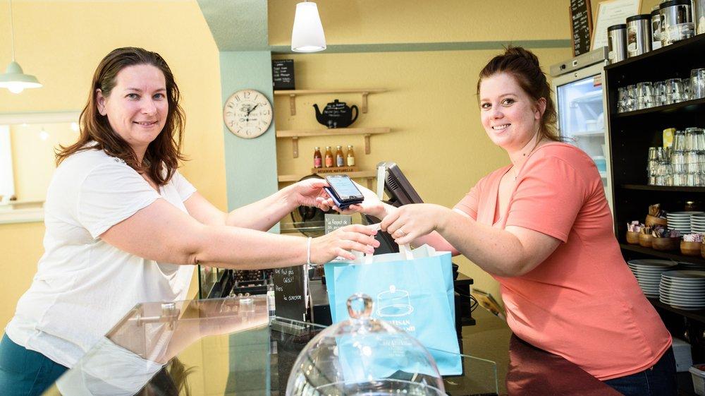 Vendeuse de L'Artisan Gourmand à Saint-Prex, Hélèle Honoré (à dr.) remet un panier à Nataliya Urtikova, utilisatrice de Too Good To Go.
