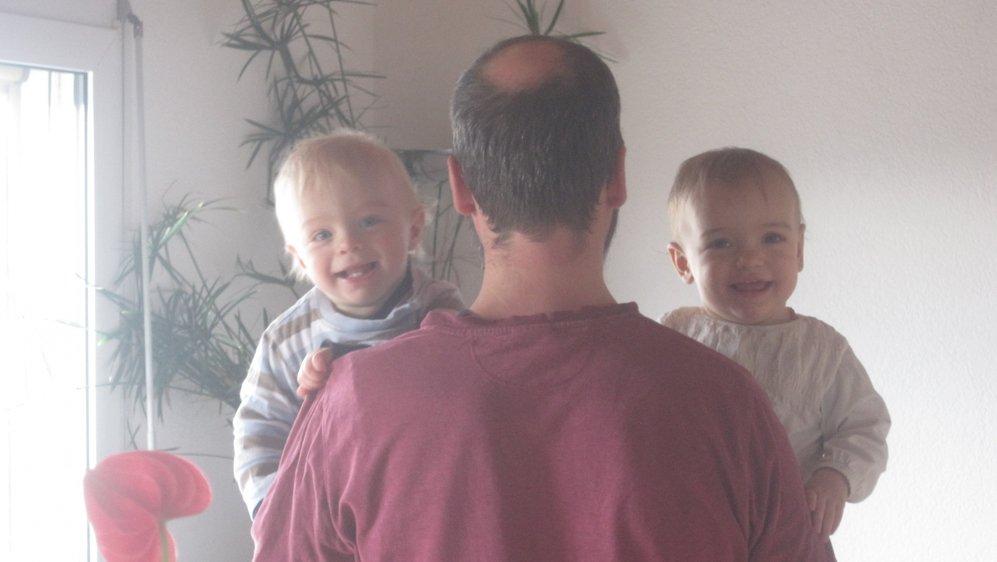 Père de trois enfants, Sébastien, à Saint-Prex , pose avec ses jumeaux, nés en 2018, cinq ans après leur frère aîné.