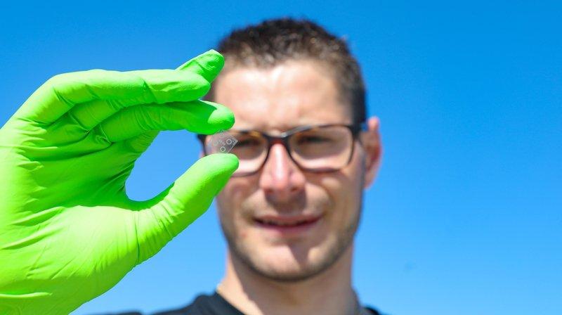 Matthieu Rüegg, doctorant à l'EPFL, tient au bout d'une pince quatre micro-résonateurs.