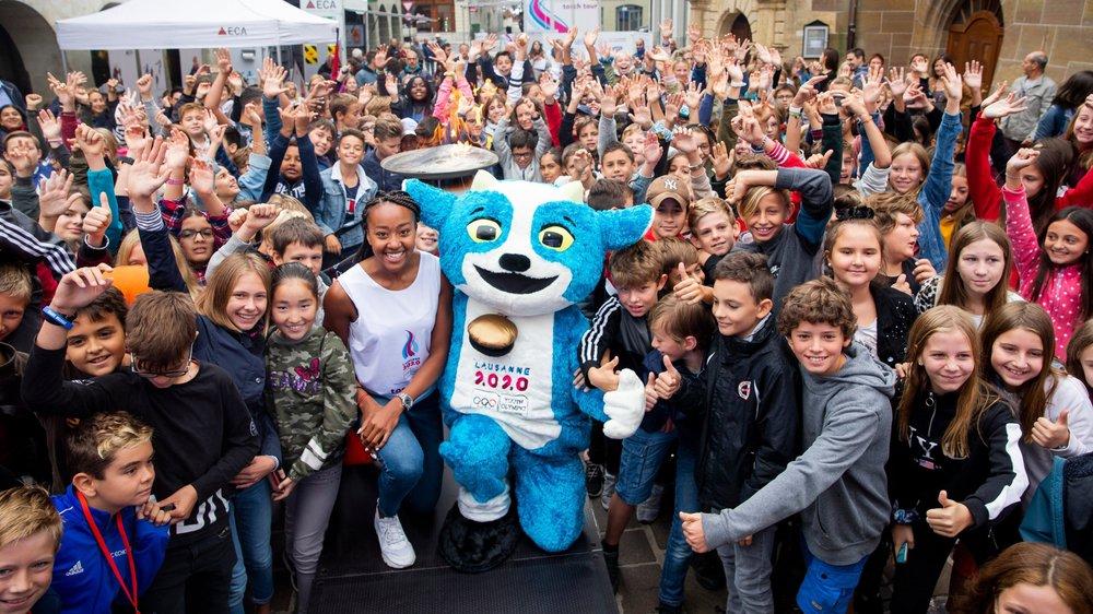 """Ambiance de fête, mardi matin au centre de Morges: les écoliers ont accueilli la flamme olympique, ainsi que la sprinteuse Sarah Atcho et la mascotte des JOJ, """"Yodli""""."""