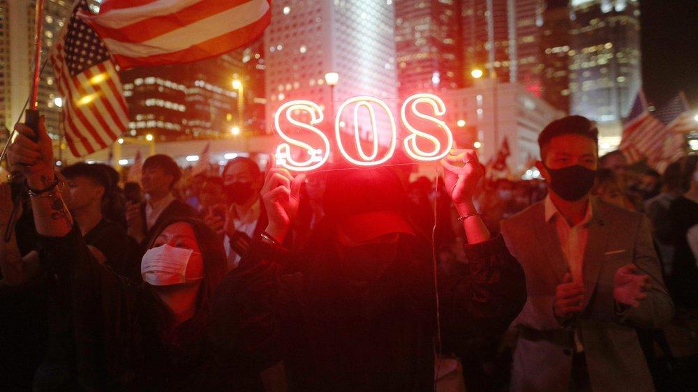 Les manifestants pro-démocratie, à Hong Kong, brandissant des signaux SOS et des drapeaux américains, hier.