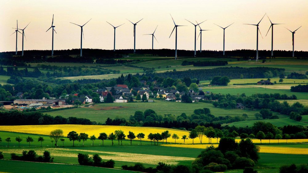 En Allemagne, dans le grand «plan pour le climat», présenté en septembre dernier, conservateurs (CDU-CSU) et sociaux-démocrates (SPD) ont prévu d'imposer une distance minimale d'un kilomètre entre les éoliennes (ici vers Schleiden, près de la frontière belge) et les habitations (groupe de cinq  maisons minimum). Ceci doit autant s'appliquer pour le neuf que pour le remplacement d'une vieille éolienne par une neuve, plus puissante.