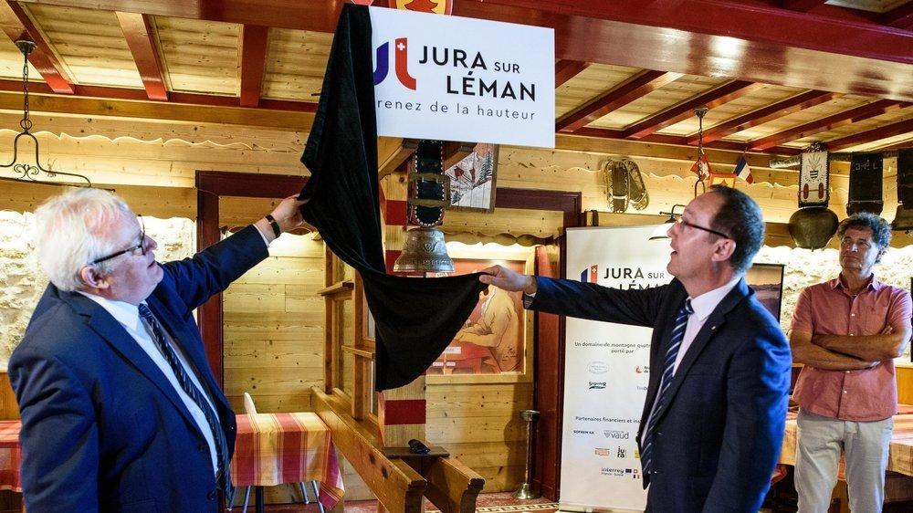 """Clément Pernot, président du Conseil départemental du Jura et Gérard Produit, responsable politique du tourisme au sein de Région de Nyon, dévoilent le nouveau nom """"Jura sur Léman"""" et son logo devant Thierry Genoud, président de Télé-Dôle."""