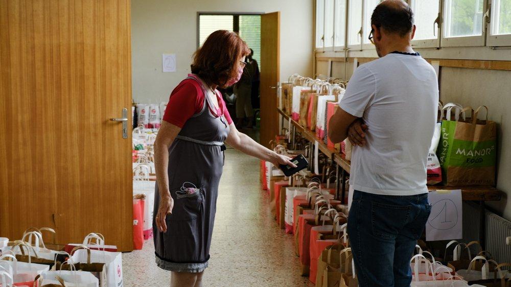 Bien organisés, les bénévoles distribuent deux sacs de nourriture puis une sélection de produits ménagers.