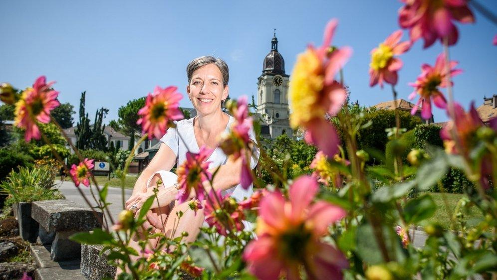 """Véronique Hermanjat, qui pose ici vers un massif de dahlias de la variété """"Honey"""", ne néglige aucun détail."""